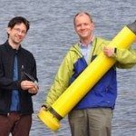 John Lyman (left) holding an XBT and Gregory Johnson (right) holding an Argo Float. Both are used to measure ocean heat content.