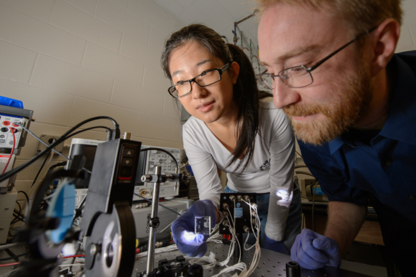 Researchers Richard Lunt and Yimu Zhao test cutting edge transparent solar cells at their Michigan State University lab