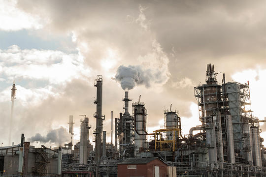 Smoke rising from oil refinery. (California)